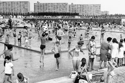Zomerse drukte op het Sloterparkbad aan de Sloterplas, omstreeks 1965. Op de achtergrond de flats aan de Noordzijde van de Sloterplas, naar ontwerp van Piet Zanstra. Foto: Dienst der Publieke Werken.