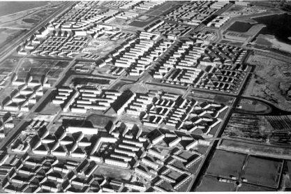 Luchtfoto van Geuzenveld in noordoostelijke richting; 1962. Op deze foto is de open bebouwing die zo typerend is voor het Nieuwe Bouwen duidelijk te zien. De woningen zijn zo gebouwd dat er voldoende lucht, licht, ruimte en groen is.