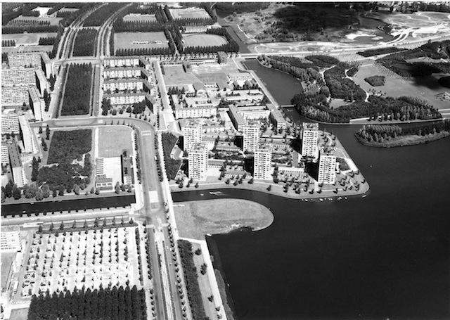 Luchtfoto van de Tuinstad Osdorp aan de oever van de Sloterplas. In het midden is Meer en Vaart, rechts daarvan de zes flats van Torenwijck; augustus 1974. Foto: Dienst der Publieke Werken.