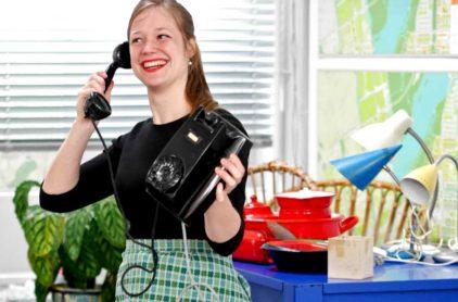 Verkoop Tussen Kunst & Vintage. Vrijwilliger Jennifer toont telefoon. Foto: Anna Ietswaart.